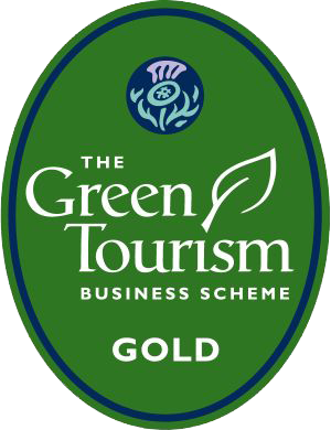 Green Tourism Gold Award logo. Green oblong circle with thistle logo at the top and the words 'The Green Tourism business scheme gold' underneath with a green leaf at the 'i' of the word tourism