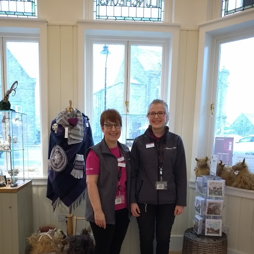 Two members of the Ballater iCentre team pose in the iCentre surrounded by Shop Local and retail produce