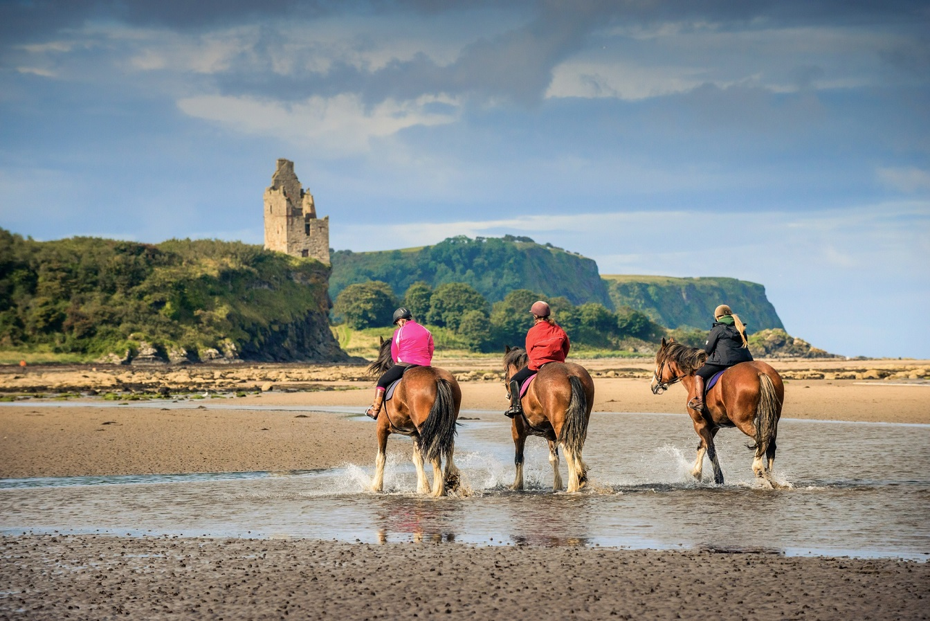 Three horses are ridden through the water on a beach with ruin of castle in background