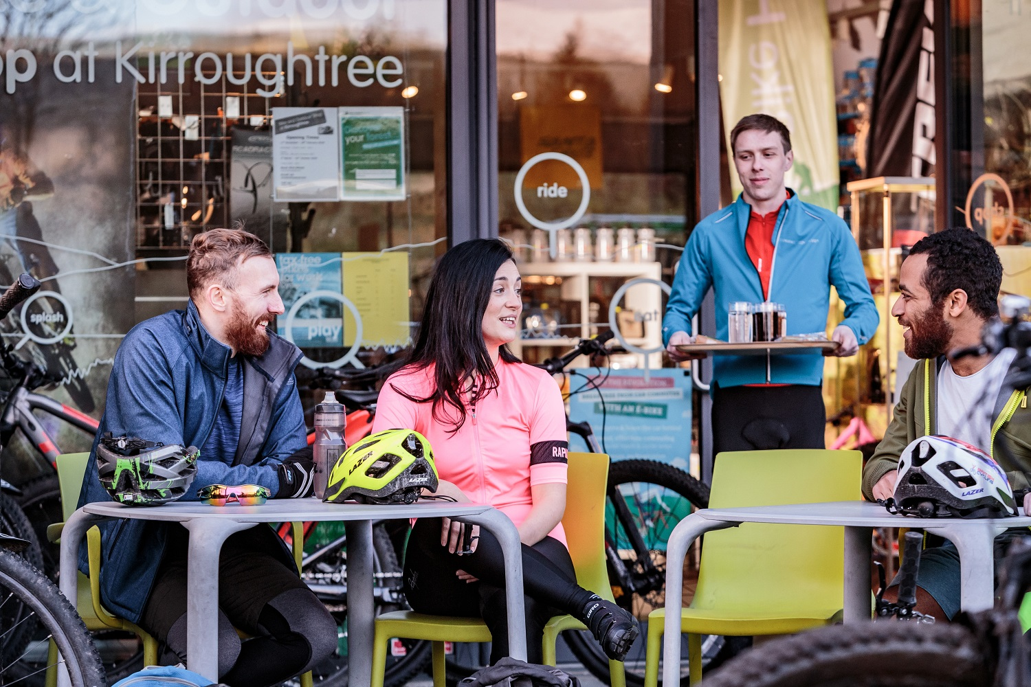 People sitting down and talking at a cafe in Kirroughtree Visitor Centre with their cycling equipment out