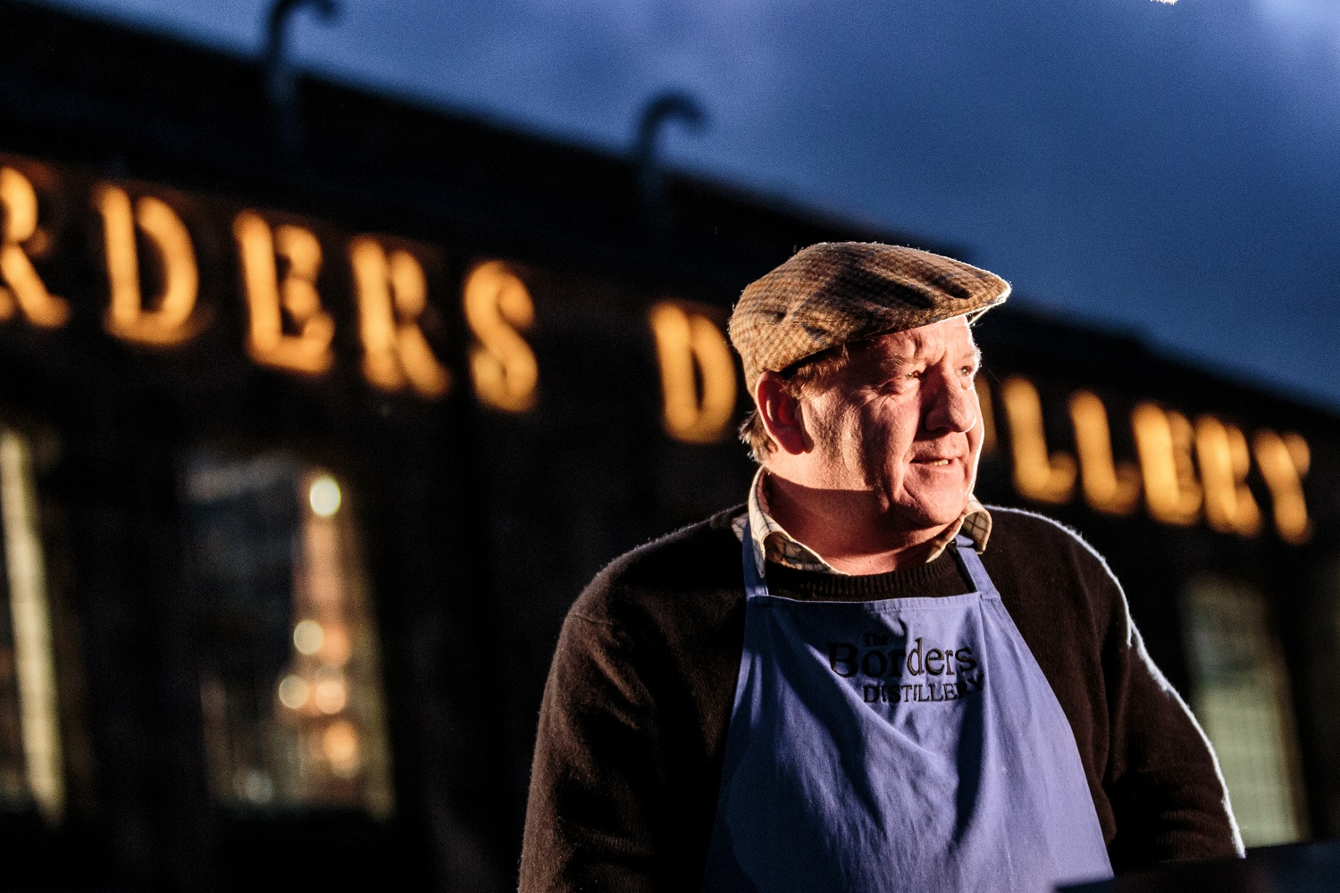 John Fordyce standing in front of the Borders Distillery wearing a flat cap and apron
