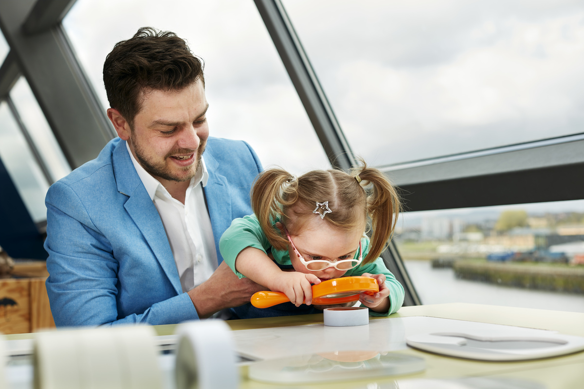 A man and his young daughter with additional needs explore the Glasgow Science Centre