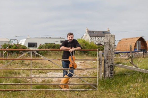 Musician Jamie Macdonald leans on fence with a violin in hand in front of farm house