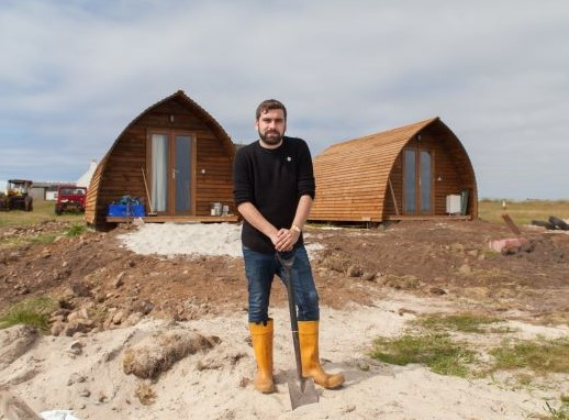 Musician Jamie Macdonald stands in front of two cabins resting a shovel on the sand