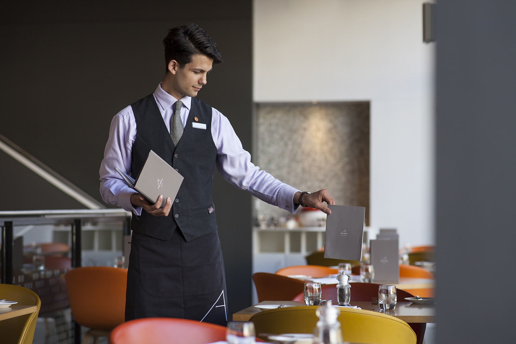 Joe Posnett lays out menus on cafe tables at the Apex Hotel