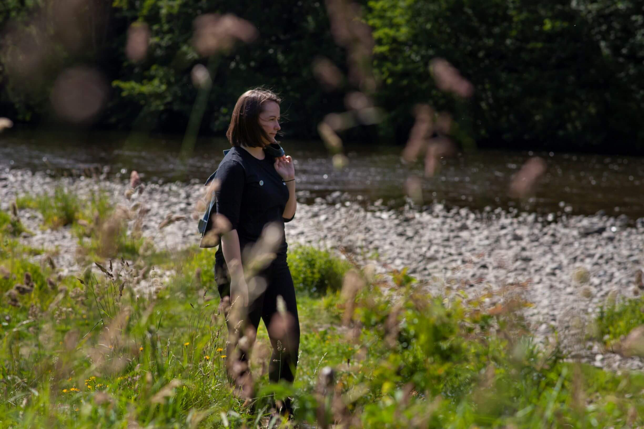 Shannon McFarlane of Tempest Brewery walks beside a river in the sunshine with grasses in the foreground