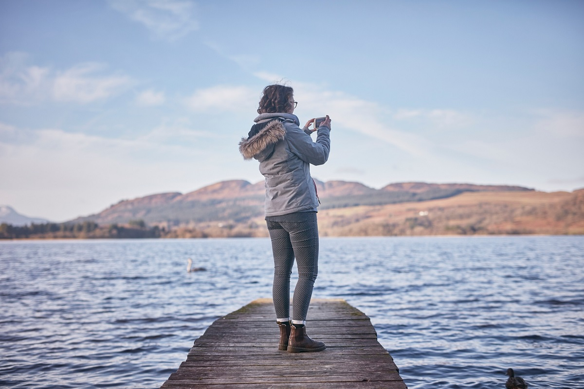 Woman standing on pier taking picture of loch